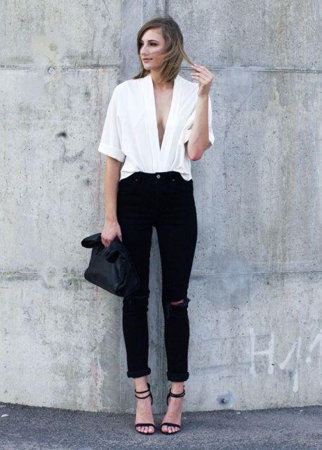 Modelo usa calça preta, blusa branca com decote generosos, bolsa e sandalia preta.