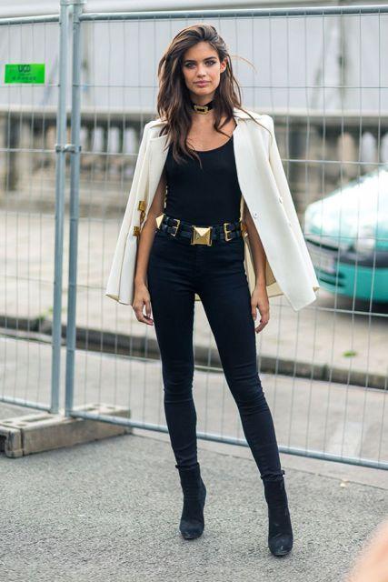 Modelo usa ankle boot preta, calça preta cintura alta com cinto dourado, blusinha preta e blazer branco.