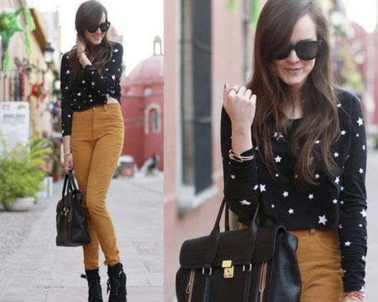 Modelo usa blusa preta estampad de branco, calça caramelo, bota e bolsa preta.