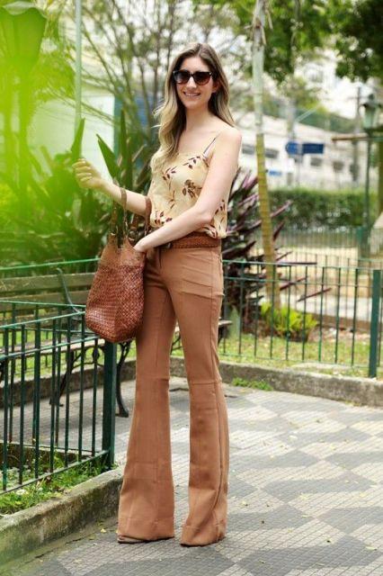 Modelo usa blusinha estampa nude, calça marrom flare, cinto marrom e bolsa marrom.