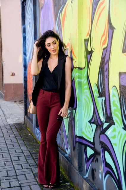 Modelo usa blusa e colete preto com calça vermelho vinho de cintura alta.