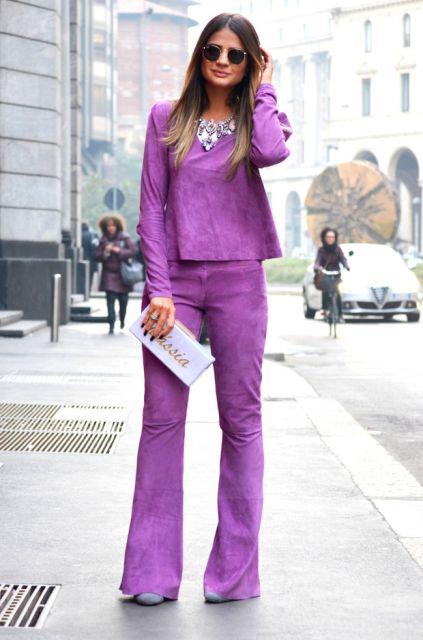 Modelo usa calça e blusa manga longa roxa com bolsa lilás.