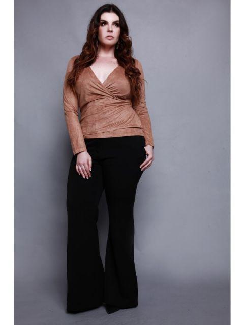 Modelo usa calça preta flare, e blusa em tons terrosos.