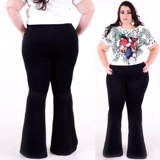 Modelo usa calça flare preta e blusa estampada de manguinhas branca.
