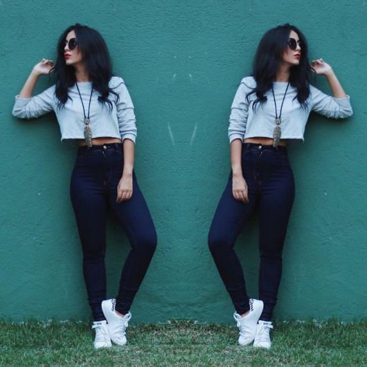 Modelo usa calça jeans azul escuro, blusinha cropped manga longa cinza e tenis branco.