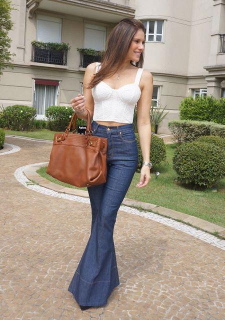 Modelo veste calça jeans flare azul, cropped de alças branco e bolsa marrom.