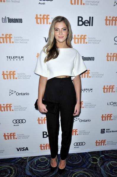 Modelo usa calça social cintura alta preta, blusa cropped branca e sapato preto.