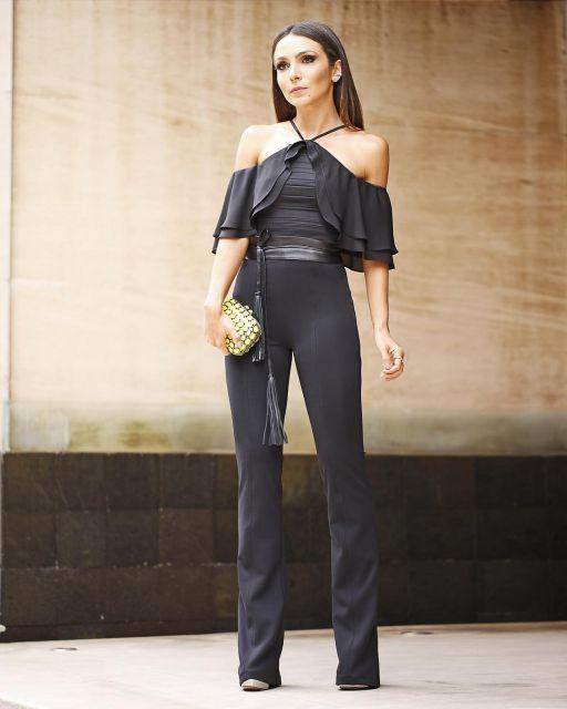 Modelo usa body de babados nas mangas, calça flare preta e bolsa dourada.