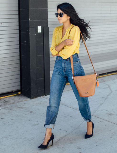 Modelo veste calça jeans cintura alta, blusa amarela e sapato preto com bolsa na cor caramelo.