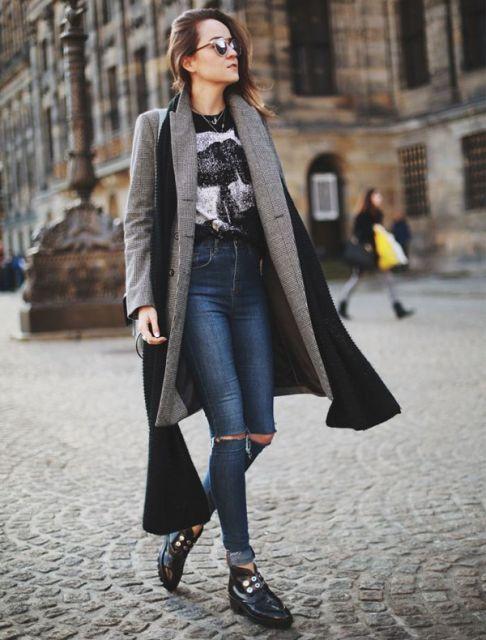 Modelo usa casaco cinza longo, botinha preta blusa preta estampada e calça jeans cintura alta com joelhos rasgados.
