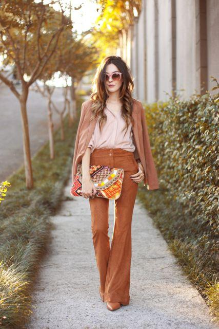 Modelo usa calça suede flare, blusa nude, jaquetinha suede e bolsa colorida.