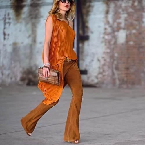 Modelo usa blusa de um ombro só caramelo, calça caramelo e bolsa em tom caramelo também.