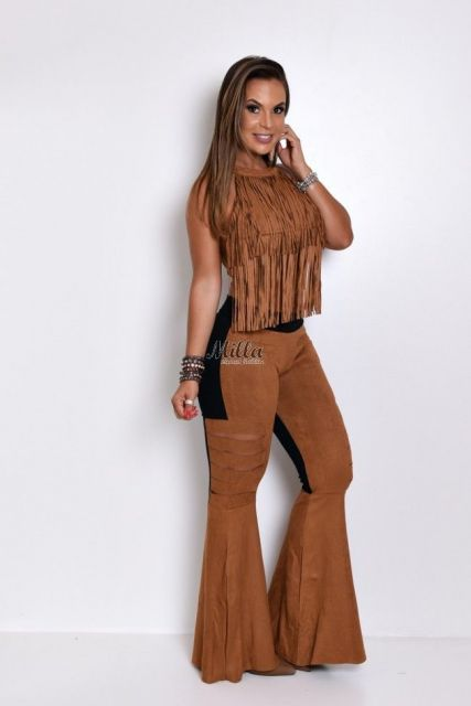 Modelo usa calça suede preto e caramelo modelo flare, blusa de franjas suede caramelo.