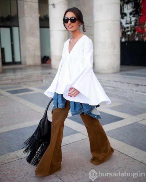 Modelo usa calça suede flare marrom, blusa larga branca e bolsa preta de franjas.