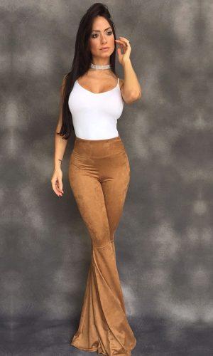 Modelo usa blusa de alcinha branca simples, calça flare suede marrom.
