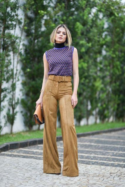 Thássia Naves usa blusa regatinha roxa, calça cintura alta suede marrom e bolsa preta e laranja de mao.