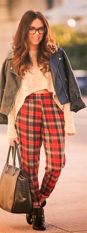 modelo usa cropped de la manga longa,, jaquetinha, calça xadrez vermelha, bolsa e botinha.