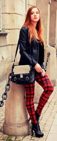 Modelo usa calça xadrez, bolsa de couro, jaqueta e botinha preta em couro.