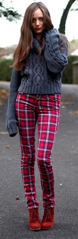 modelo usa calça vermelha xadrez e bota na mesma cor.
