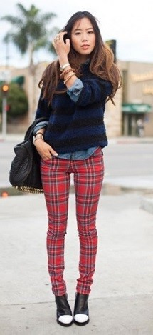Modelo usa calça xadrez vermelha, camisa, sobreposição azul, e bota preta estilo cuturno.