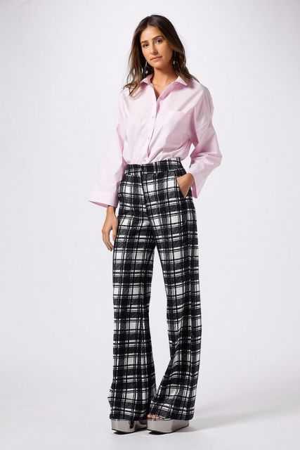 Modelo veste camisa rosa, calça xadrez e sandalia plataforma.