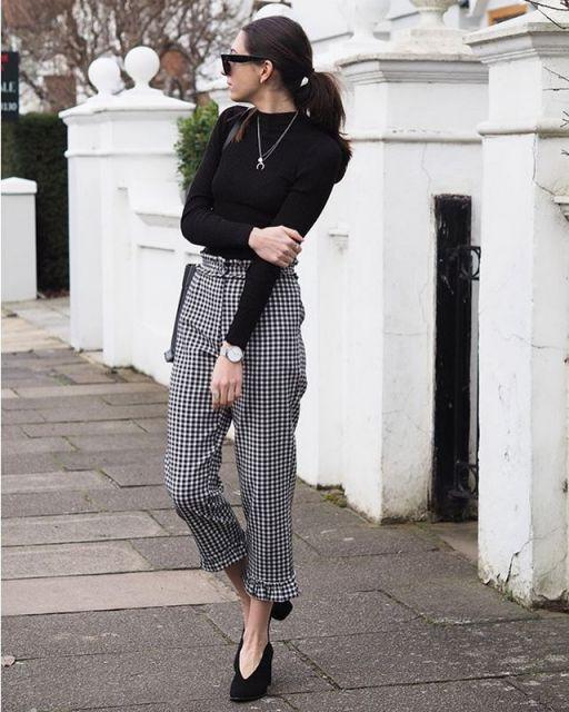 Modelo usa calça xadrez, meio cinza com blusinha e sapato preto.