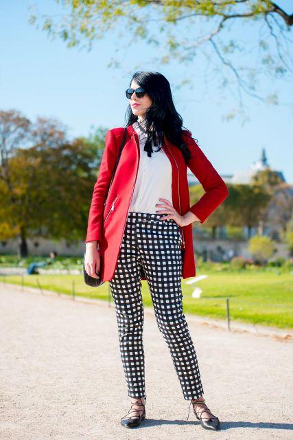 Modelo usa calça preta xadrez, blusa branca, casaco vermelho e sapatilha.
