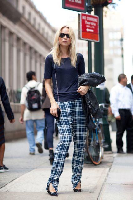 Modelo veste calça em tons de azul marinho e claro, blusinha manga curta, sapatinho de salto, bolsa pequena alça corrente.