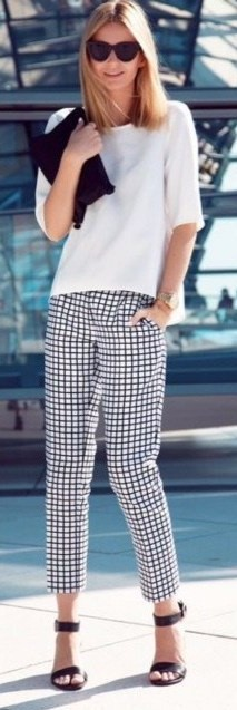 Modelo veste calça xadrez branca, com blusa branca, sandalia preta e carteira no mesmo tom.