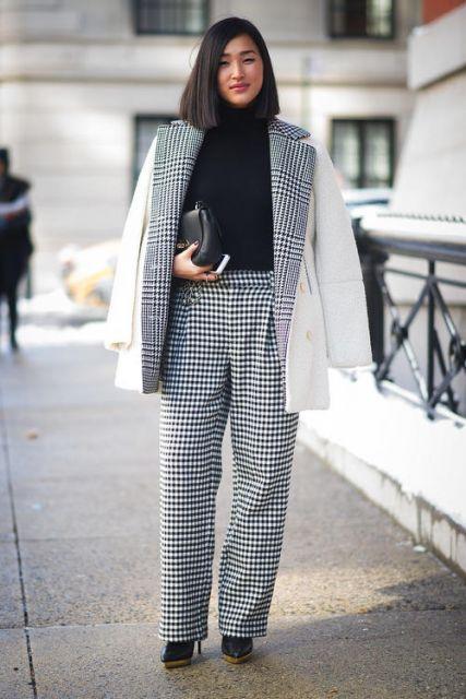 Modelo veste calça xadrez branca, blusa e sapato preto e blazer branco com detalhes em xadrez.