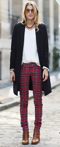 Modelo usa clça vermelha xadrez, blusa branca, casaco preto e bota em cores terrosas.