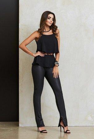 Modelo veste calça preta couro, blusa na mesma cor e sandalia preta.