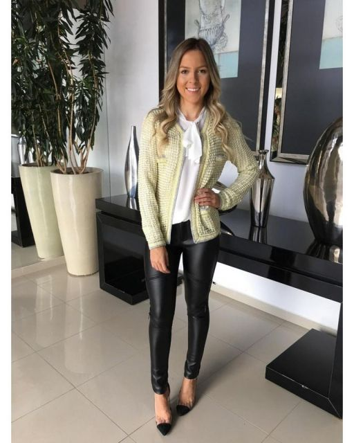 Modelo usa calça de couro, scarpin preto, blusa branca e blazer.