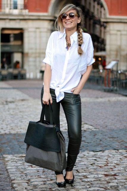 Modelo usa camisa branca, calça de couro preta, sapatilha e bolsa na mesma cor.