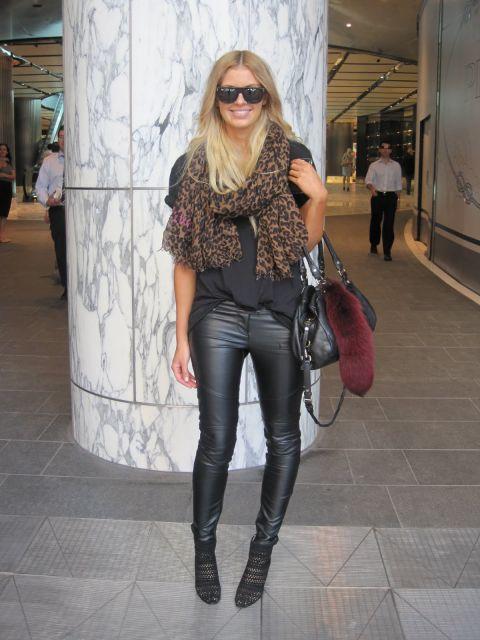 Modelo usa calça skinny de couro, blusa preta, botinha e bolsa preta.