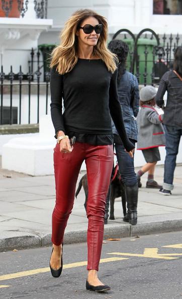 Modelo veste calça de couro vermelha, blusa manga longa preta e sapatilha na mesma cor.