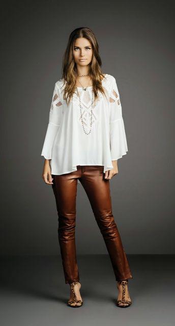 Modelo usa blusa bata larguinha branca e sandalia marrom com calça na mesma cor.