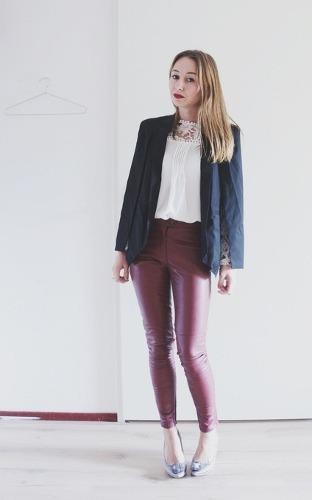 Modelo usa calça marrom, blusa branca, blazer preto e sapato prata.