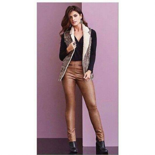 Modelo usa calça marrom, sapato preto, blusa na mesma cor e coletinho de pelinhos.