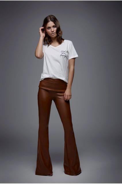 Modelo veste calça marrom de couro e blusa branca camiseta.