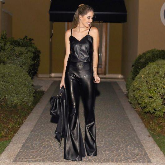 Modelo usa blusa preta de alcinha, calça preta flare de couro e jaqueta.