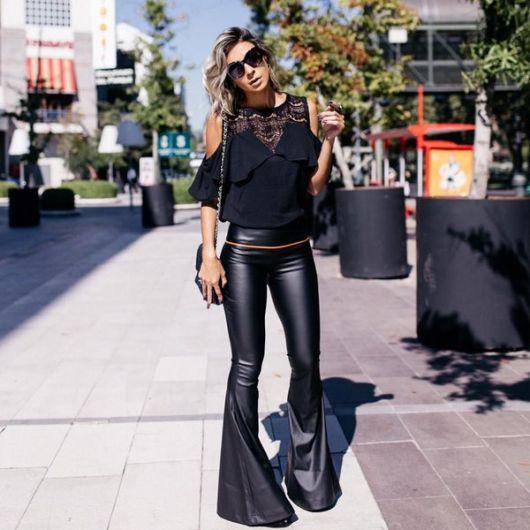 Modelo usa blusa vazada preta, calça flare preta e bolsa de ombro preta.