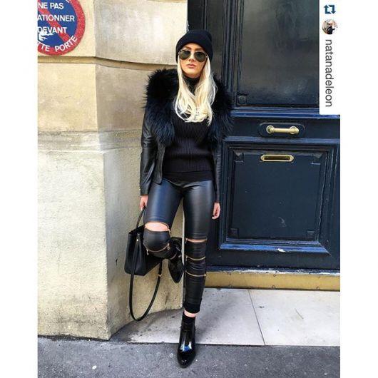 Modelo usa calça com ziper preta de couro, casaco na mesma cor de pelinhos, bolsa e sapato na cor preta também.