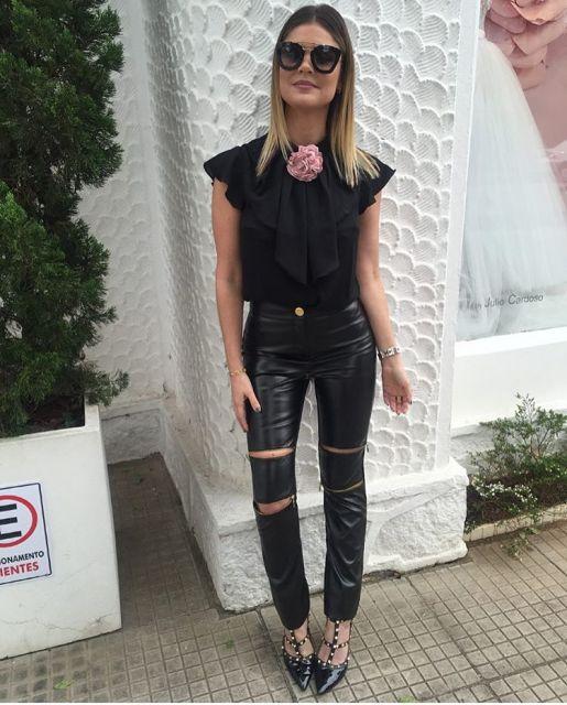 Modelo usa calça preta de ziper, sapato preto bico fino com spikes e blusa preta basica com detalhe de rosa como shocker.