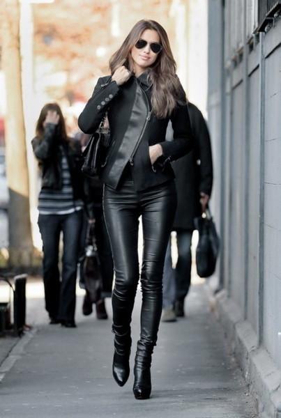 modelo usa jaqueta preta com detalhe de couro, calça de couro e bota preta de couro.