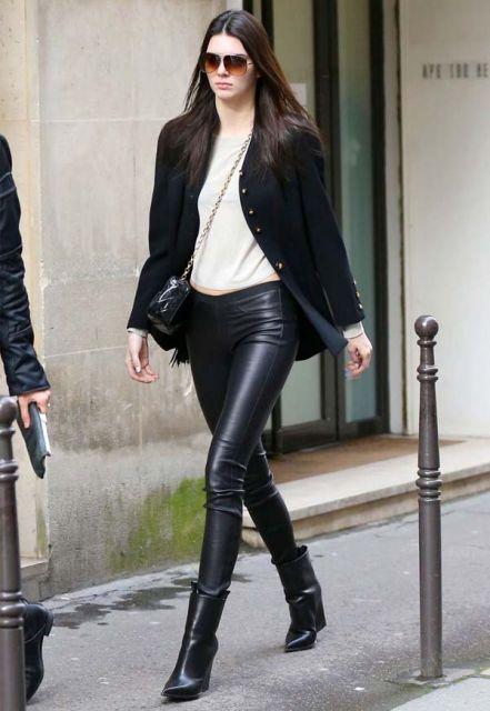 Modelo usa botinha preta, calça de couro, blusa branca e blazer.
