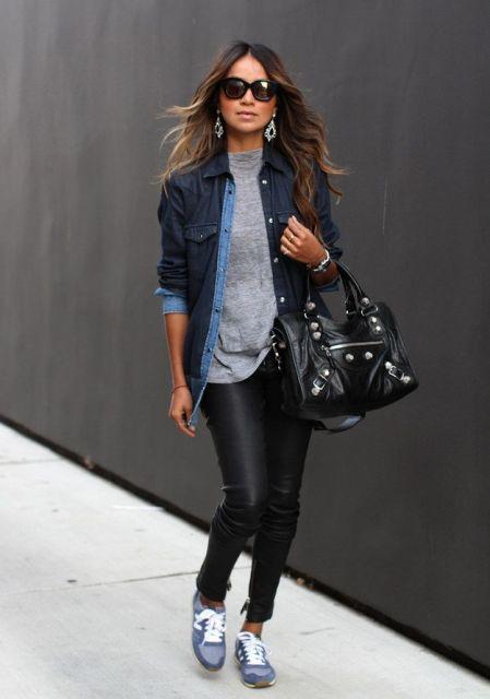 Modelo usa camiseta cinza, calça preta de couro, tenis e jaqueta azul com bolsa preta.