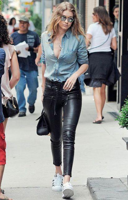 Modelo veste calça preta de couro, jaqueta jeans e tenis branco.