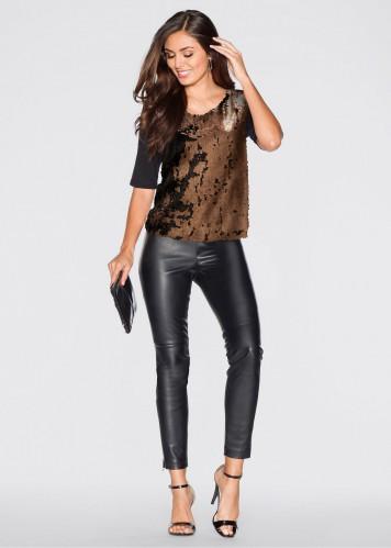 Modelo usa calça preta, sandalia preta e blusa em tons terrosos.