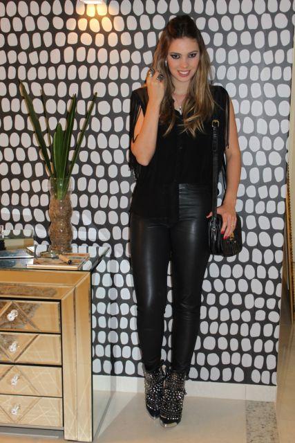 Modelo usa claç de couro preta, blusa preta, bolsa preta e sapato com brilhos.
